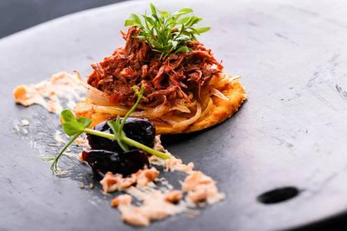 Cachapas Cebolla y Ciruelas Caramelizadas Carne mechada de Cabrito Crema de Anacardo